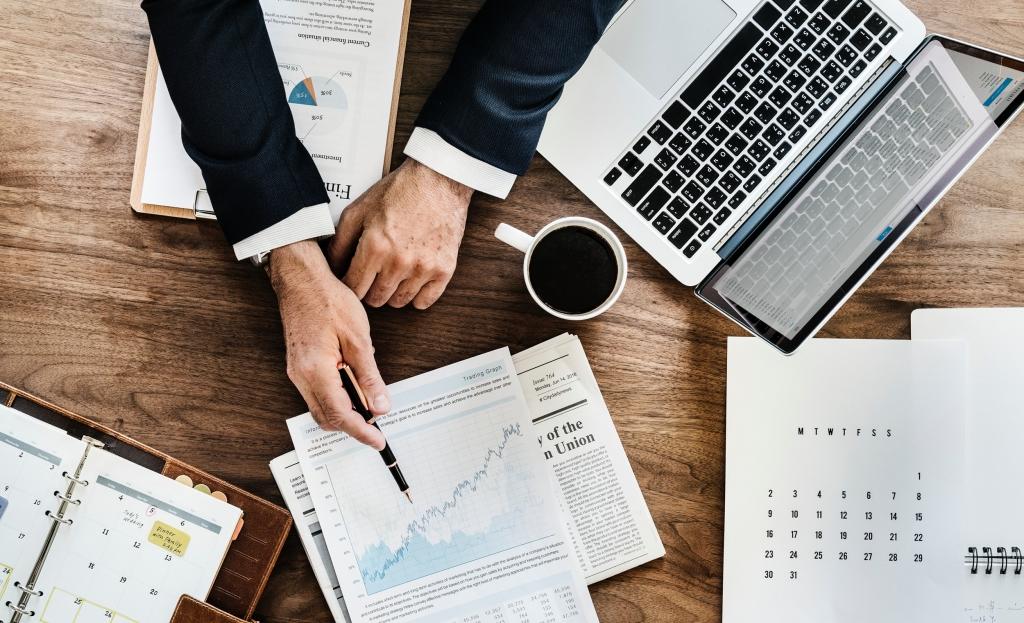 Laptop, Kaffeetasse und Männerhände in Anzug, die auf eine Börsenkurs-Grafik zeigen