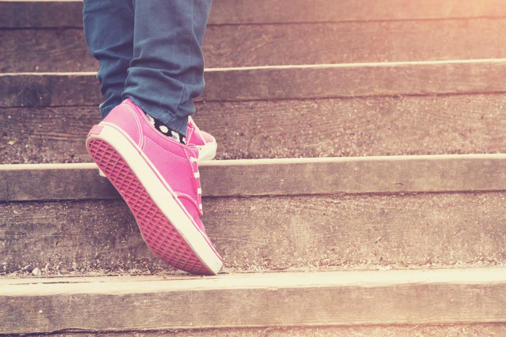 Person in pinken Schuhen geht Stufen hinauf