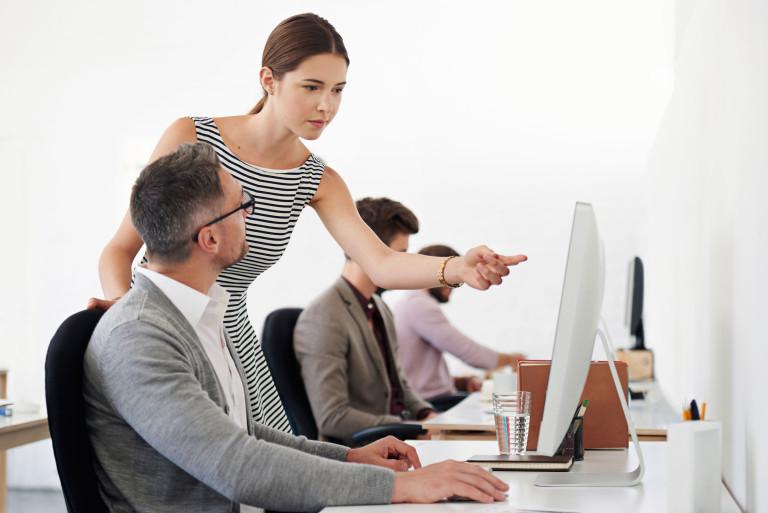 Stehende dunkelhaarige Frau erklärt vor dem Computer sitzenden Mann etwas und zeigt auf den Bildschirm