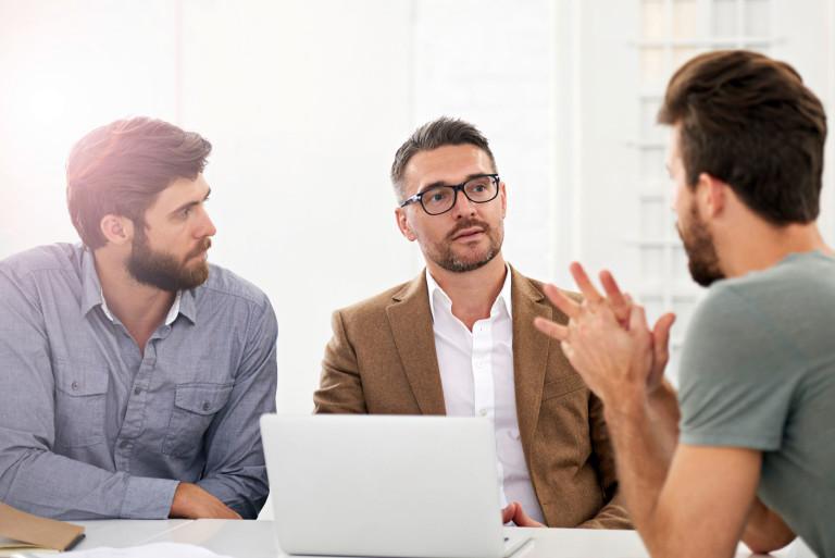 3 Männer sitzen um einen Laptop herum und sprechen miteinander