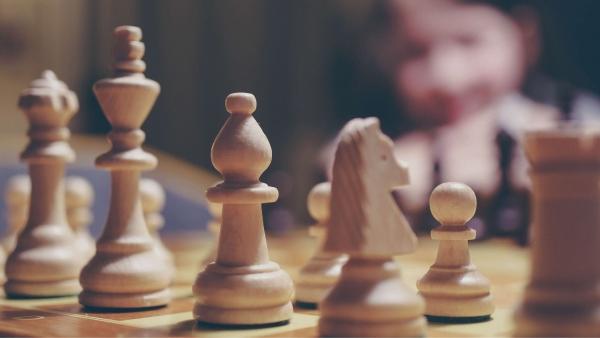 Schachfiguren aus hellem Holz stehen auf Schachbrett