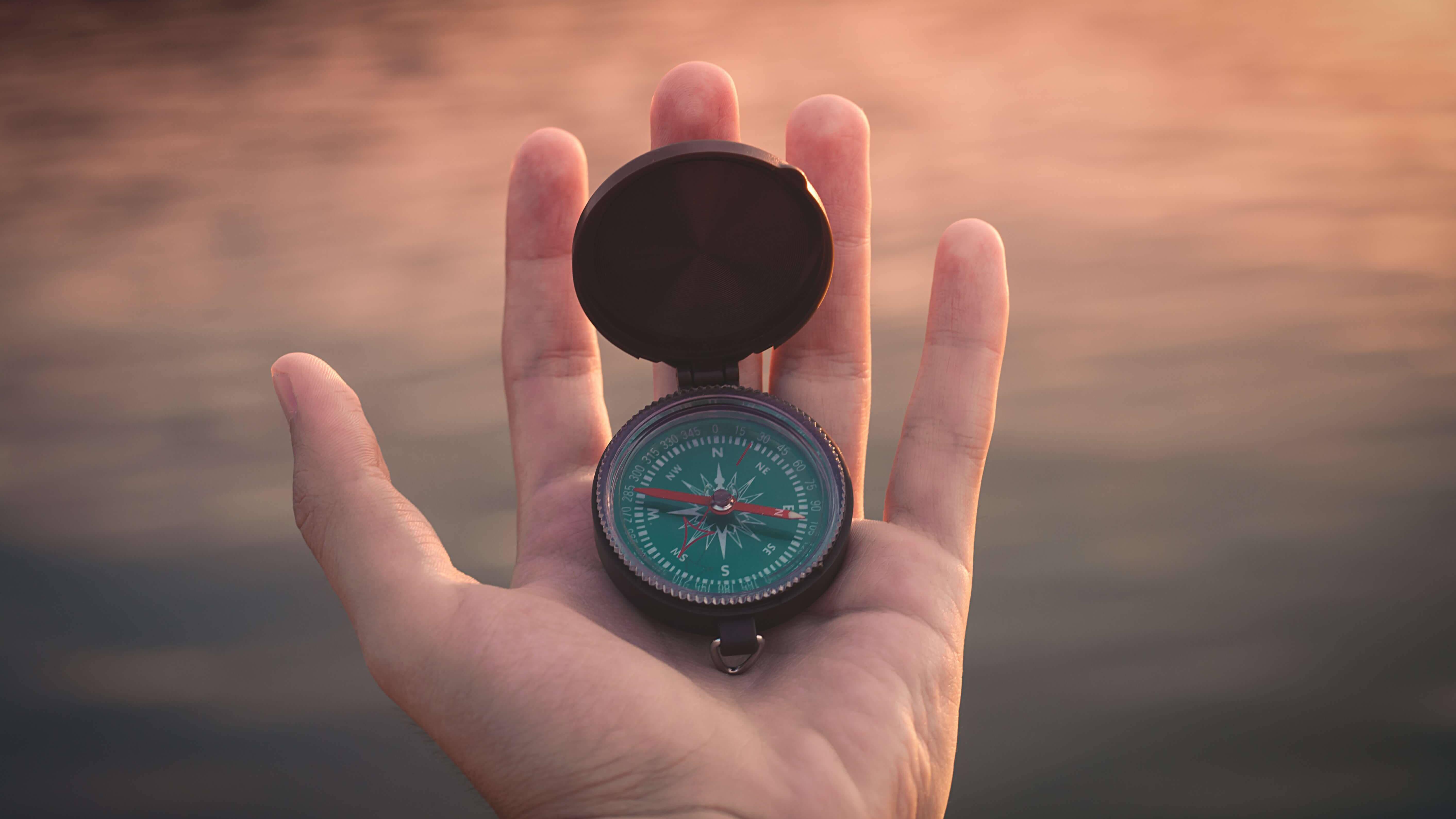 Kompass in einer Hand, im Hintergrund Wasser