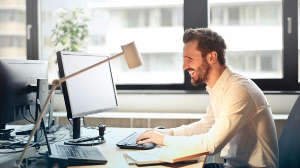 Mann sitzt lächelnd am Schreibtisch und schreibt ein E-Mail