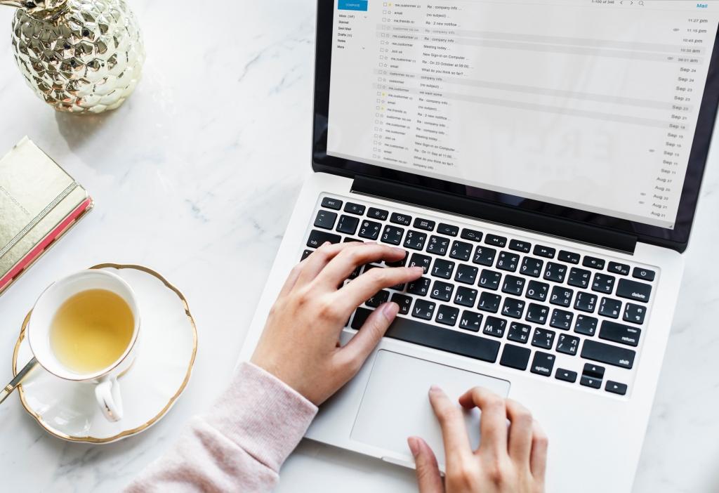 Hände auf einem Laptop neben einer Tasse Tee