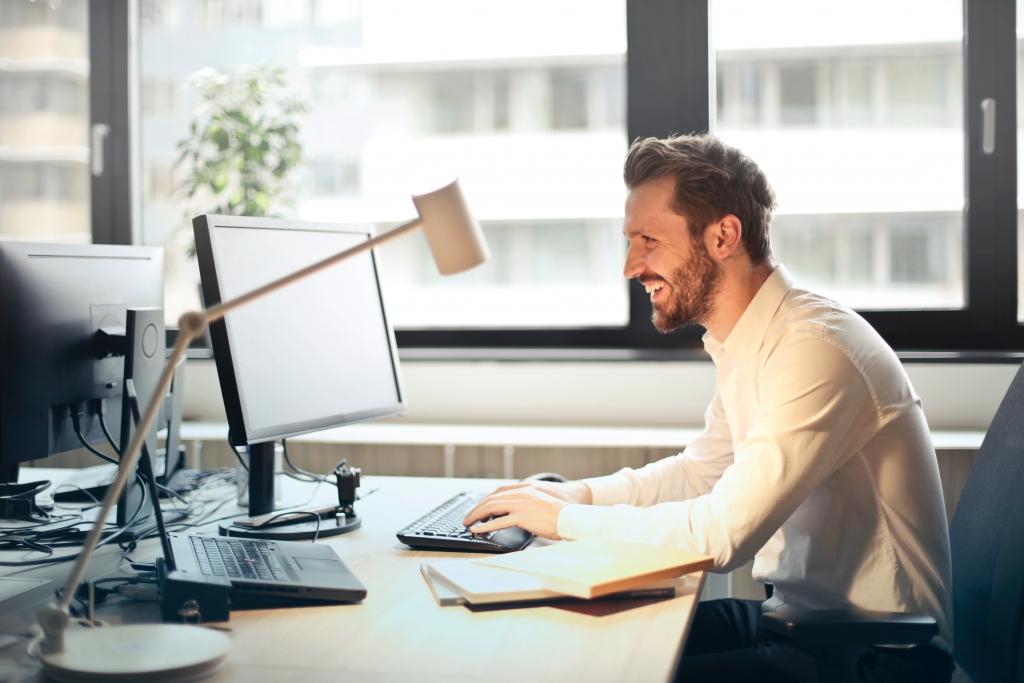Lächelnder Mann am Schreibtisch vor einem Computer-Bildschirm