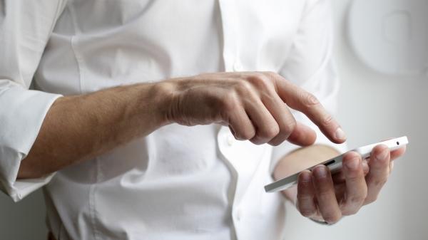 Männerhand tippt auf einem Smartphone